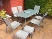 Glass top garden table, six chairs and two foot stools.