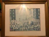 Print of a Lowry painting of a street scene in muted colours. Gold coloured frame with glass front