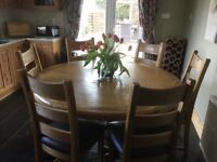 Large round oak dining table with six oak chairs