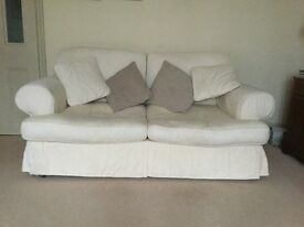 Two matching three seater sofas, cream fabric loose washable covers. Includes spare set of covers.