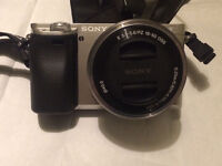 Sony A6000 compact camera in silver with lens and accessories
