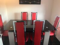 Dining room table with glass top and 6 red chairs
