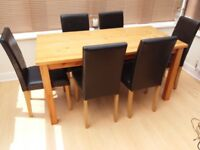 Solid wood table with 6 brown faux leather chairs. Good clean condition