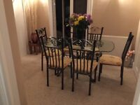 Elegant modern glass top dining table and matching upholstered chairs. 6' x 3'. Buyer to collect