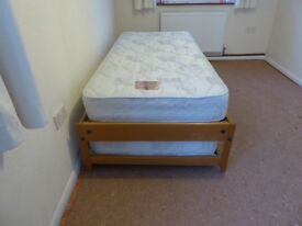 single pine bed with a second roll out single bed under