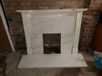 White marble fireplace surround and hearth, with wood mantelpiece