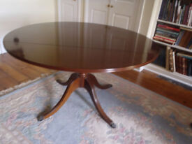 1970's Mahogany Table. Round with 2 drop sides and claw feet. Seats 6