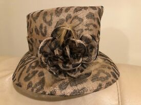 LADIES HAT- UNUSUAL DESIGN BROWN BEIGE LEOPARD PRINT WITH FLOWER/FEATHERED DECORATION