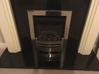 Modern gas fire with cream marble surround and black marble harth.