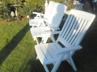 three reclining white garden chairs with red cushions