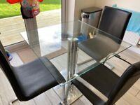 Square glass dining table with three faux leather chairs