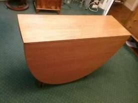 Nathan solid teak oval drop leaf dining table.