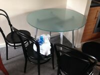 MODERN STYLE GLASS DINING TABLE WITH 4 BLACK BENT WOOD CHAIRS GOOD USED CONDITION FREE DELIVERY