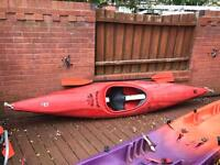 Perception Dancer kayak red with paddle and spray deck.