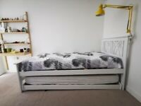 White bed with trundle bed