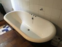Cast iron roll top bath with claw feet and white enamel finish