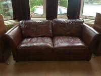 Red brown leather Sofa with pullout bed and arm chair.