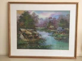 Framed scenic picture of a man in a Sampan rowing up to a fishing village