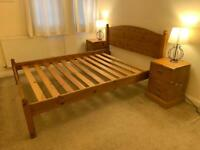Large wooden bed with wooden bedside draws
