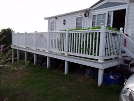Static caravan caravan wrap around decking front and side including steps and gate.