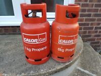 2 red propane gas bottles .one empty one half full.