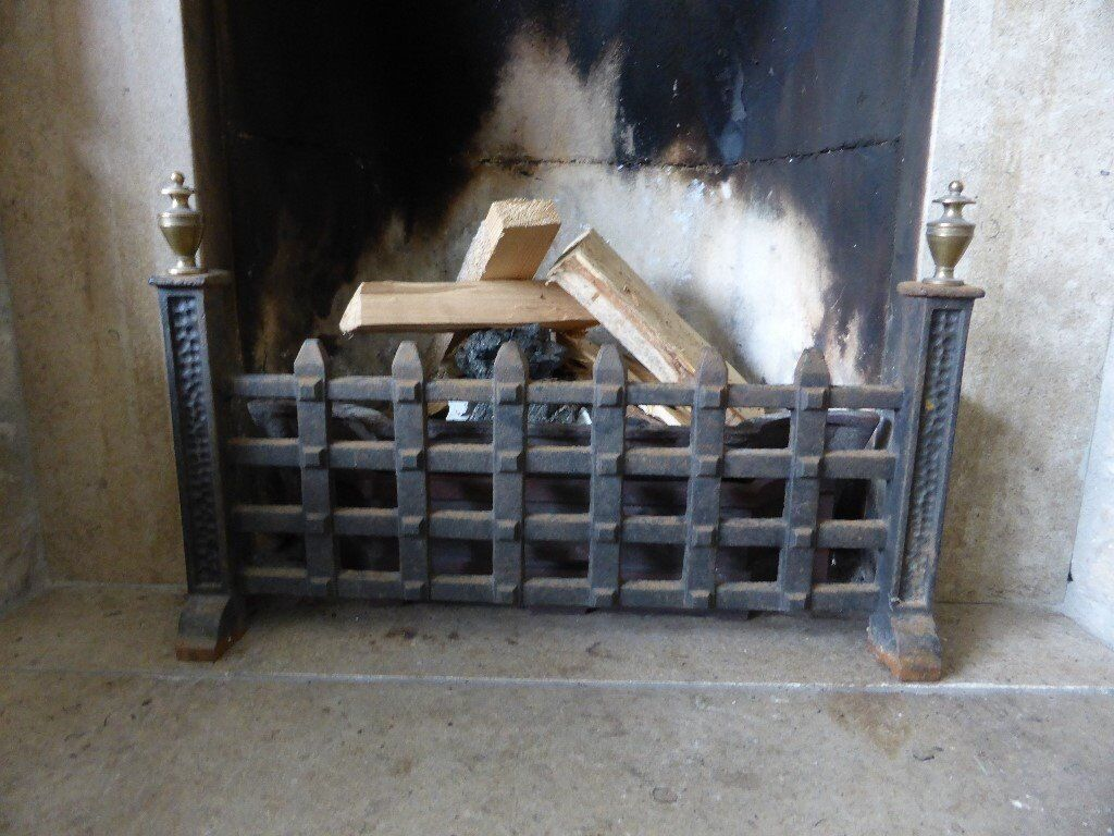 black wrought iron fireplace front grill with brass knobs in