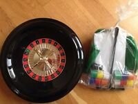 Roulette wheel with chips and green cloth