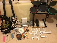 Wii console with 2 guitar hero guitars, drumkit and 5 games