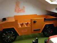 Hummer kids single bed in bright orange made of wood got toy box at front were engine would be