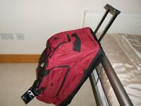 Red International Travel Holdall with wheels and pull along handle new with tags