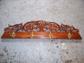 Solid brass swivelling coat hooks on a solid wooden back base.