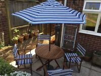 Hardwood table and chairs, including parasol and metal base.