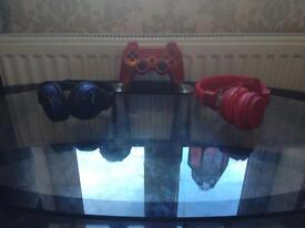 Red PlayStation 3 remote with blue and red headphones