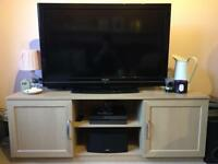TV stand. Light pine effect, silver handles. Two cupboards and two shelves. GOOD condition.