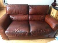 Chestnut Natuzzi leather 2 seater sofa and matching armchair.