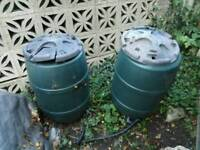 Two green water butts with lids
