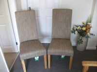 Two Oatmeal weave upholstered dining chairs.
