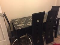 A glass Table with 6 chairs in good condition