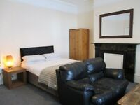 Large double bedroom with leather sofa. All-inclusive living with a weekly cleaner