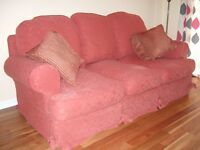 sofa, chairs and footstool in terracotta red.