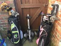 2 sets of golf clubs and 2 trolleys