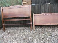 PAIR OF ANTIQUE SOLID OAK ENGRAVED HEADBOARDS WITH CASTORS