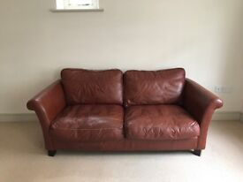 Three-seater brown leather sofa