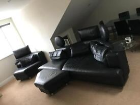 Large black leather sofa with footstool & glass table