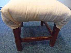 tiny stool with a padded seat.