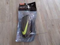 Brand new Nike hard shell slip in shin guards Size S/P