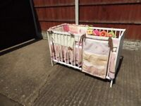 White wooden crib with bumper valance & accessory bags.