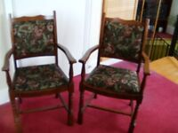 Two dining room chairs -with arms. Dark wood, dark leaf pattern on seat and back.