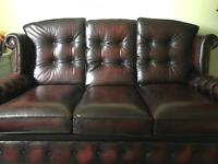 Red Chesterfield style leather sofa