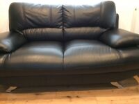 Black leather two seater sofa with footstool